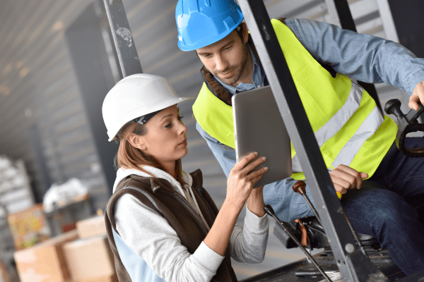 Male and female retail workers looking at a tablet in an inventory room