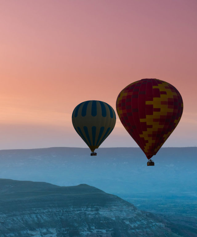 Two hot air balloons floating over mountains with a colorful sky