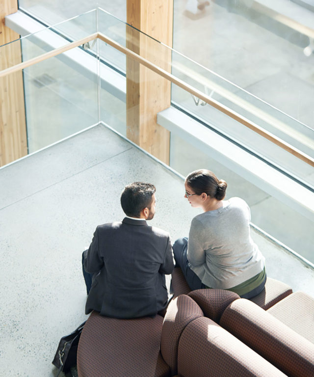 Overhead view of a man and woman sitting on a couch and talking